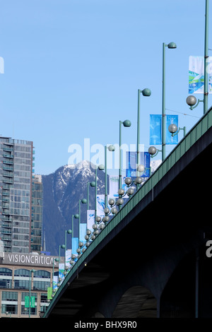 View of Olympic fags lining the Cambie street bridge looking toward the mountains. - Stock Photo