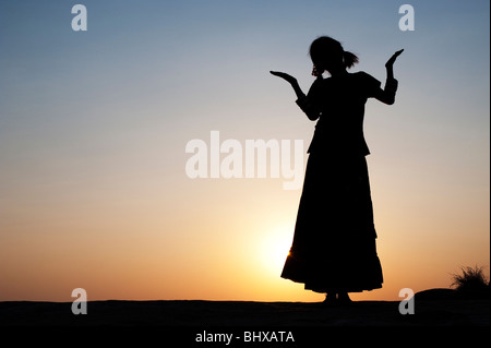Indian girl silhouette in an unconcerned carefree pose. India - Stock Photo