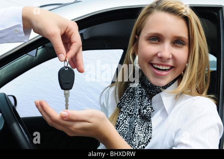 happy woman, owner of a new car receiving the car keys - Stock Photo