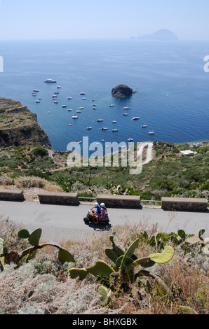 A tourist couple riding on a moped on the island of Salina, overlooking a boat filled bay, in the Aeolian Islands, - Stock Photo