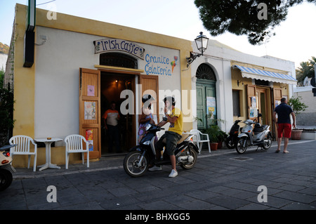 An Italian couple on a motor scooter stop at a gelateria in the town of Malfa on the Aeolian island of Salina, Sicily, - Stock Photo