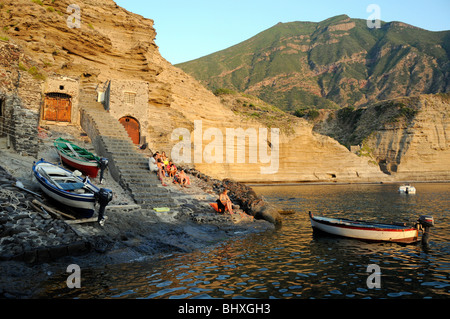 An Italian family sitting on stone steps leading to the lagoon below the village of Pollara, on the island of Salina, - Stock Photo