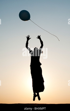 Silhouette of a young Indian girl catching a balloon at sunset - Stock Photo