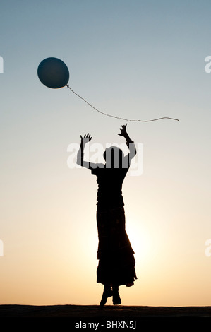 Silhouette of a young Indian girl playing with a balloon at sunset. India - Stock Photo