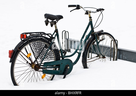 A bicycle parked in the snow - Stock Photo