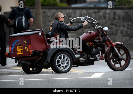 A biker arrives at a Harley Davidson rally in Weston-Super-Mare UK on a three wheeled motorcycle - Stock Photo