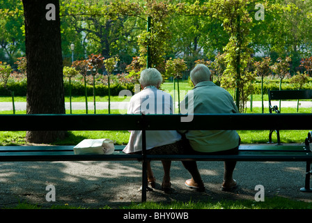 Senior couple sitting and relaxing on park bench, rear view - Stock Photo