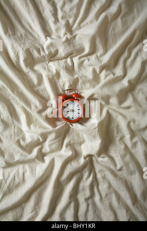 Red Alarm clock on a wrinkled duvet. Nice time, or lateness concept shot that looks good at a large size - Stock Photo