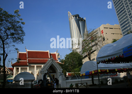 Buddhist temple and Central World skyscrapers in central Bangkok, Thailand. - Stock Photo