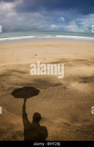 Shadow of a man holding up an umbrella on a beach during a storm - Stock Photo