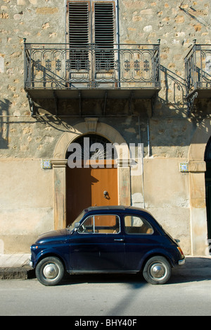 Fiat 500 Car parked outside entrance to traditional Italian building in Sicily - Stock Photo