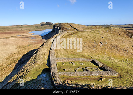 On the line of Hadrian's Wall above Milecastle 39 looking towards Highshield Crags and Crag Lough. - Stock Photo