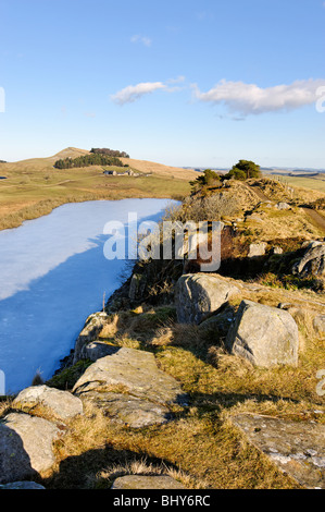 On the line of Hadrian's Wall looking down from Highshield Crags on to frozen Crag Lough. - Stock Photo