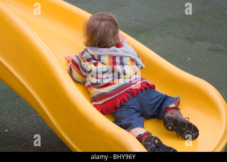 16 month old baby girl is lying on the yellow plastic slide - Stock Photo