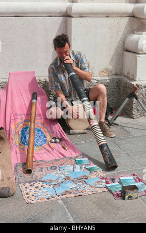 Young Caucasian male street musician playing folk music with wind instrument bamboo oboe - Stock Photo