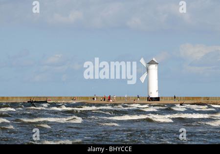 Beacon 'Windmill' on stone pier next to port entry in Swinoujscie at Baltic Sea, Poland - Stock Photo