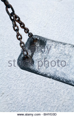 A swing lies still covered in snow in a children's play area. - Stock Photo