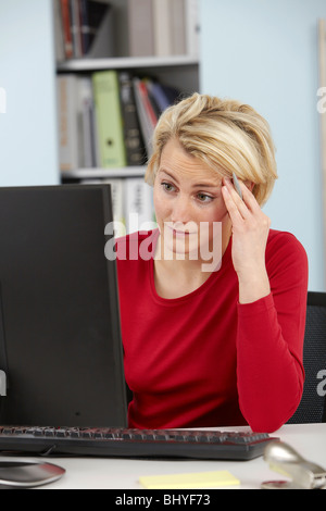 Perplexed woman in front of the computer - Stock Photo