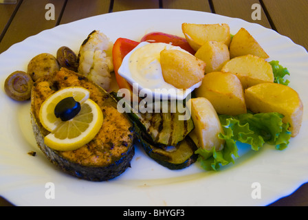 Grilled salmon steak and oven potatoes in a restaurant in Klaipeda Lithuania Europe - Stock Photo