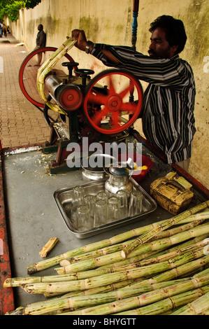 Man making sugar cane juice. Bangalore, India - Stock Photo