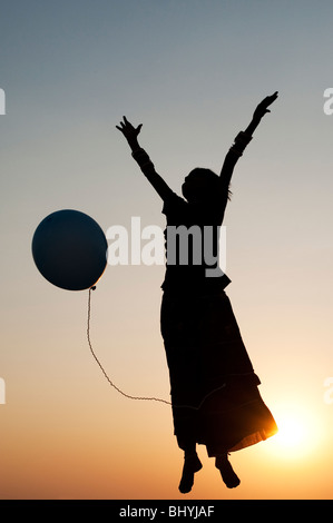 Silhouette of a young Indian girl playing with a balloon at sunset - Stock Photo