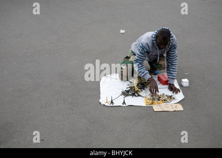 Street seller sets up his stall of Eiffel Tower souvenirs for sale on the pavement by the Sacre Coeur, Paris - Stock Photo