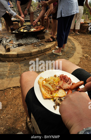 Limpopo, South Africa, family eating breakfast meal outdoors, cooking food on campfire, people, safari, background, - Stock Photo