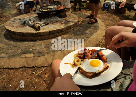 Limpopo, South Africa, tourists on safari enjoying bush breakfast cooked on camp fire, food, meal - Stock Photo