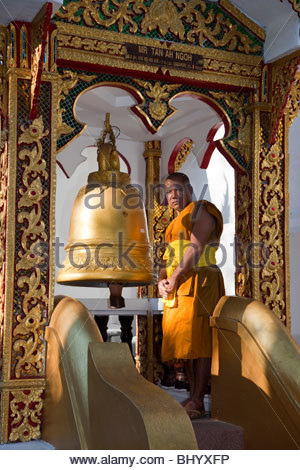 Monk at the  Buddhist Temple and prayer bellls.  Wat Phradhat Doi Suthep, Chiang Mai, Thailand. - Stock Photo