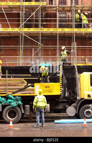 Scaffolders workmen erecting scaffold on a building in London wearing safety helmets and Hi Viz jackets - Stock Photo