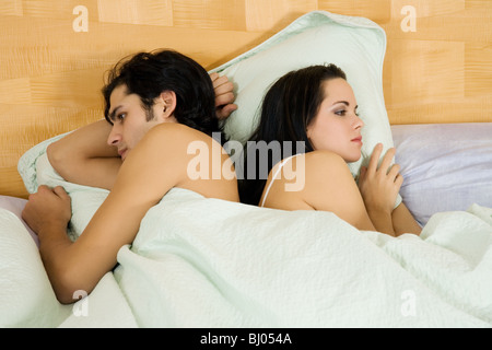 Couple disagreeing or arguing in bed - Stock Photo