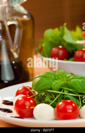 Tomato, mozzarella, rocket salad with olive oil and balsamic vinegar dressing and basil garnish shot in golden sunshine - Stock Photo