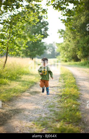 Young boy standing on a gravel road. - Stock Photo