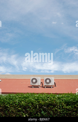 Air conditioners on a roof top between green hedge and blue sky. - Stock Photo