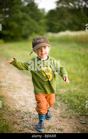 Young boy running on a gravel road. - Stock Photo