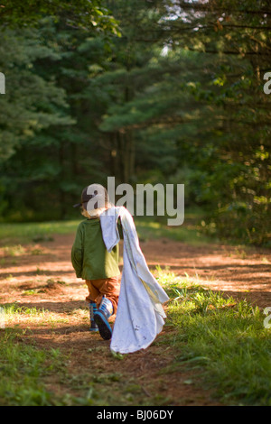 Young boy carrying a blanket in the woods.