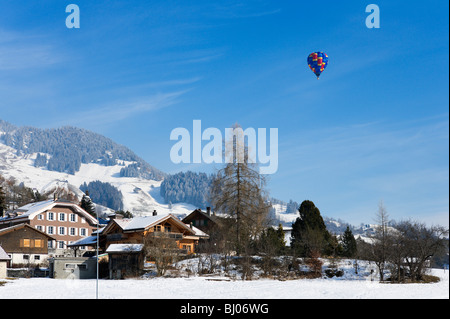 Single hot air balloon over the town during the January Balloon Festival, Chateau d'Oex, Vaud, Switzerland - Stock Photo