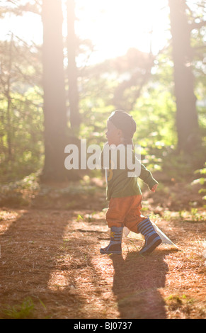 Young boy carrying a blanket in the woods. - Stock Photo