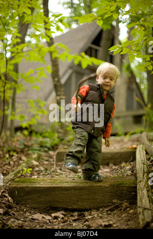 Young boy climbing down stairs in the woods, carrying a stick. - Stock Photo