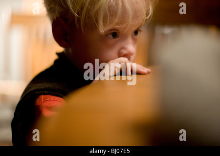 Young boy leaning on edge of table in thought. - Stock Photo