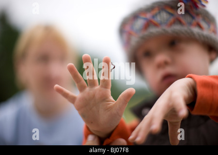 Young boy looking at an inchworm crawling on his hand. - Stock Photo