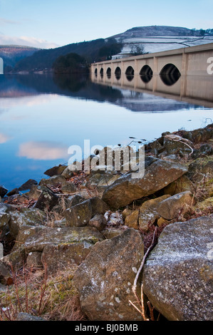 Ashopton Viaduct carrying the A57 over Ladybower Reservoir in the Peak District is reflected in the icy cold water. - Stock Photo