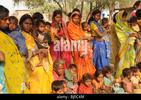 Mothers wearing saris and traditional Indian clothing and their children watching in line - Stock Photo