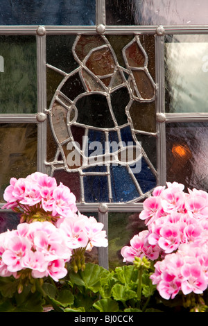 Stained glass window and flowers, Lohr am Main Germany - Stock Photo