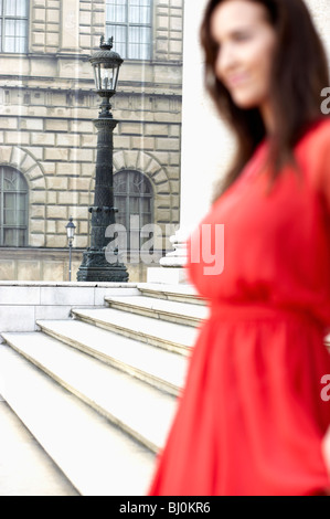 young woman in red dress standing in front of theatre - Stock Photo