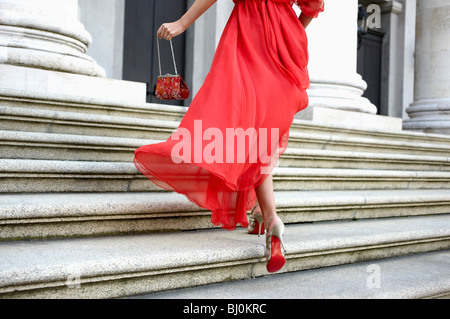 detail of young woman in red dress running up stairs of theatre - Stock Photo