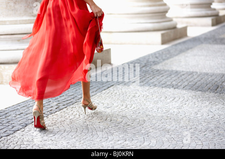 detail of young woman in red dress running through arcades of theatre - Stock Photo
