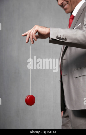 businessman playing with red yoyo - Stock Photo