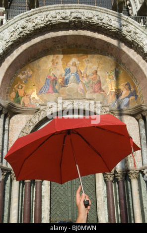Tour group guide leader leads with umbrella leads the way, signalling follow me. St Marks Square. Piazza San Marco. - Stock Photo