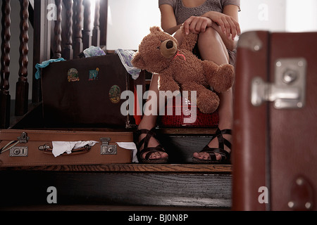 teenage girl sitting on stairs with teddy bear surrounded by suitcases - Stock Photo